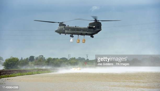 An RAF Chinook helicopter delivers sandbags to plug a gap where the River Steeping burst its banks near Wainfleet All Saints, in Lincolnshire....