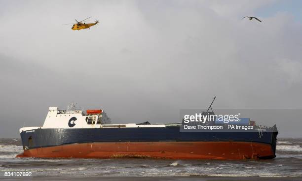 An RAF Sea King helicopter flies over the cargo ship Riverdance which has run aground at Blackpool due to the high winds It was carrying trucks and...
