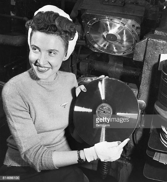 An RCA factory worker holds up the billionth RCA record produced a performance of 'Semper Fidelis' and 'Stars and Stripes Forever' by Serge...