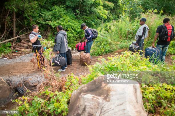 An RCMP officer talks with a group of people who claimed to be from Haiti in Champlain New York as they prepare to cross the border into Canada...