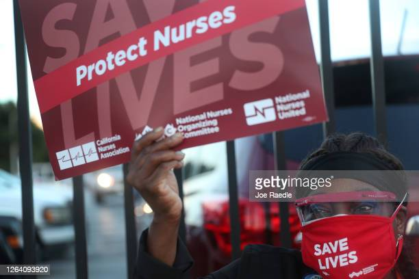 An RN joins with other demonstrators who are taking part in a national day of action to save lives during COVID19 on August 05 2020 in Miami Florida...
