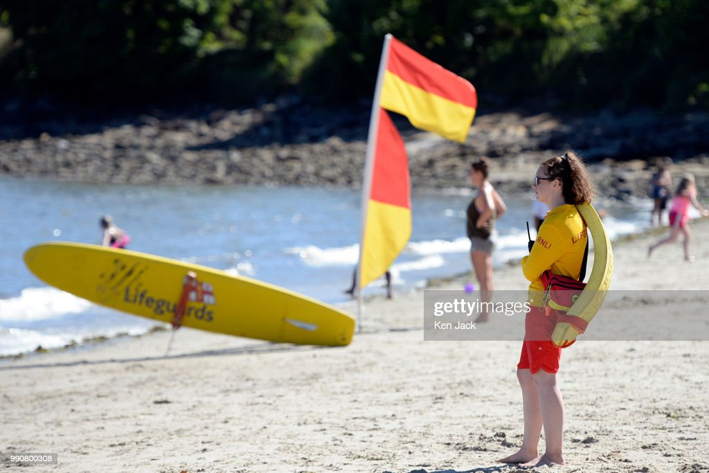 An RNLI lifeguard keeps watch as people enjoy the sun on Silver Sands beach at the start of the Scottish school holidays as the heatwave continues, on July 3, 2018 in Aberdour, Scotland.