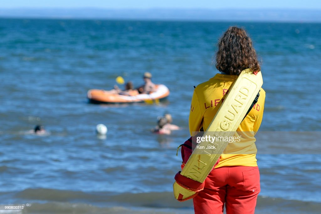 An RNLI lifeguard keeps watch looks towards an inflatable dinghy as people enjoy the sun on Silver Sands beach at the start of the Scottish school holidays as the heatwave continues, on July 3, 2018 in Aberdour, Scotland.