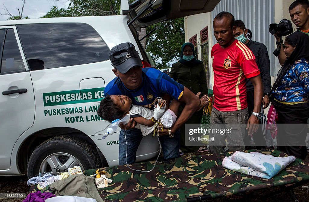An Rohingya migrant helps carry a child to an ambulance for medical assistance at a temporary shelter on May 18, 2015 in Kuala Langsa, Aceh province, Indonesia. Hundreds of Myanmar's Rohingya refugees arrived in Indonesia on May 15, many requiring medical attention. Thousands more are believed to still be stranded at sea reportedly with no country in the region willing to take them in. Myanmar's Rohingya Muslim community have long been persecuted and marginalized by Myanmar's mostly Buddhist population.