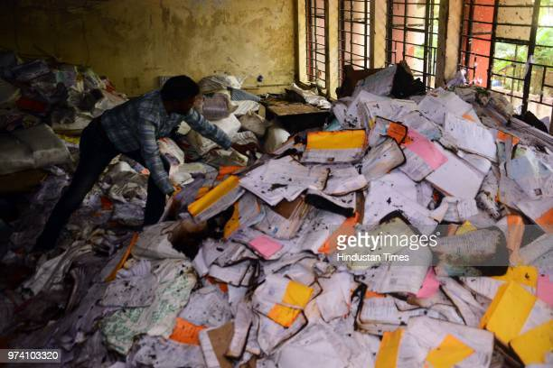 An RTO personnel inspects the papers which were damaged due to fire broke out on the first floor of the Regional Transport Office due to short...