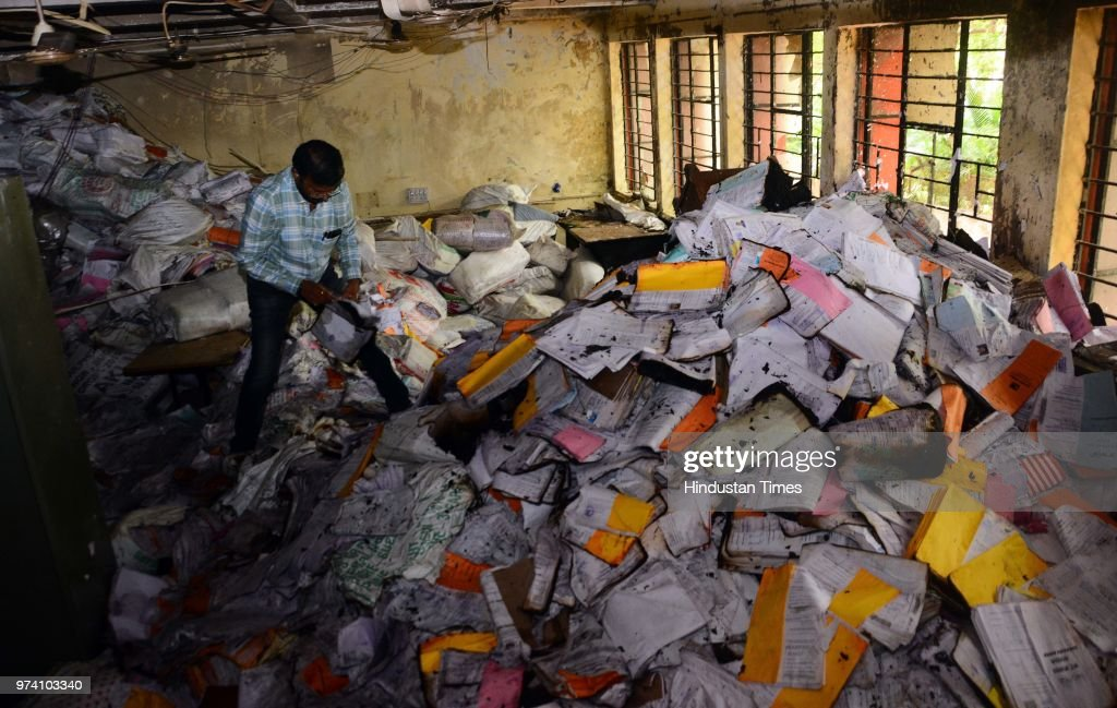 An RTO personnel inspects the papers which were damaged due to fire broke out on the first floor of the Regional Transport Office (RTO) due to short circuit, on June 13, 2018 in Pune, India. No one was injured in this incident and the situation was brought under control by the fire brigade within 15 minutes.
