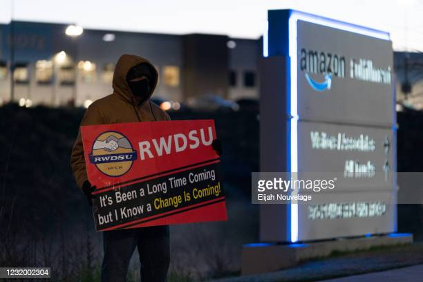 An RWDSU union rep holds a sign outside the Amazon fulfillment warehouse at the center of a unionization drive on March 29, 2021 in Bessemer,...