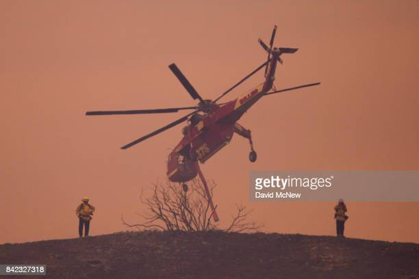 An S64E Sikorsky Skycrane firefighting helicopter flies past firefighters on a smokey ridge during the La Tuna Fire on September 3 2017 near Burbank...
