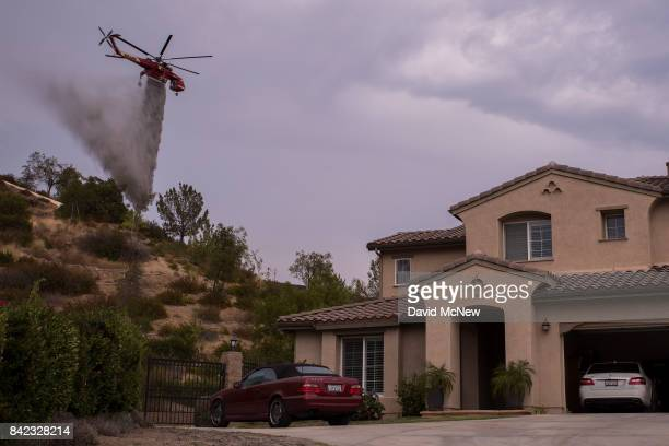 An S64E Sikorsky Skycrane firefighting helicopter makes a drop to protect a house during the La Tuna Fire on September 3 2017 near Burbank California...