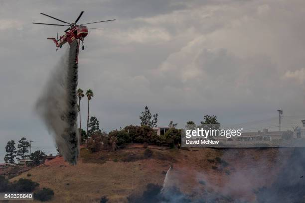 An S64E Sikorsky Skycrane firefighting helicopter makes a drop to help firefighters protect houses when a hot spot breaks out below them during the...