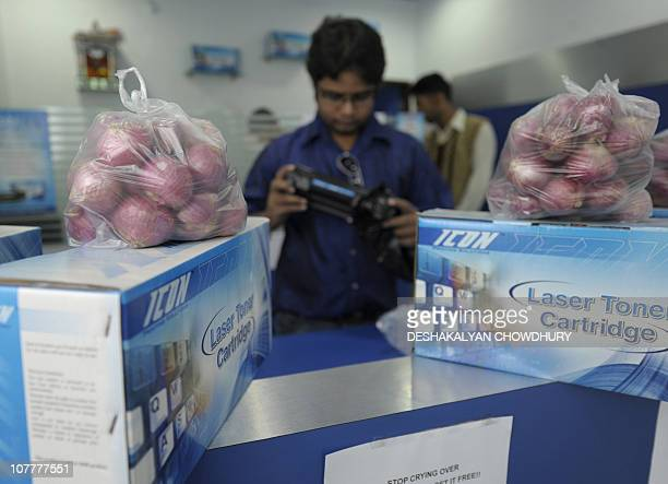 An salesman checks a printer cartridge while onion bags are offered for free with the purchase of a printer ink cartridge to attract customer inside...