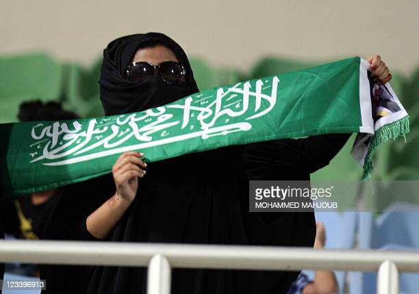 An Saudi Arabian fan holds up the national flag during the 2014 World Cup Asian zone Group D qualifying football match between Oman and Saudi Arabia...