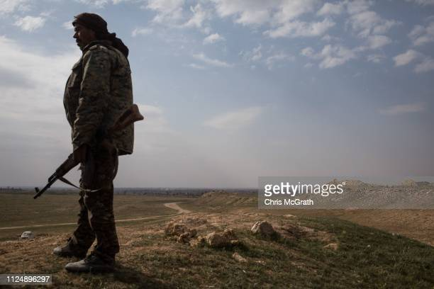 An SDF fighter looks out from a hilltop position overlooking Bagouz on February 14 2019 in Bagouz Syria Civilian numbers fleeing fighting have...