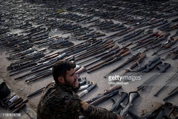 An SDF fighter looks over seized ISIL weapons that were found in the last stronghold of the extremist group as they were displayed at an SDF base on...