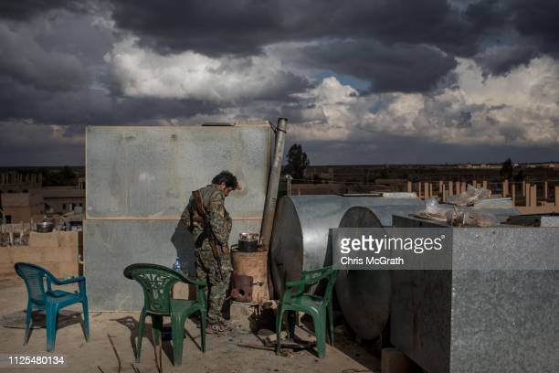 An SDF fighter makes tea on rooftop on the outskirts of Bagouz on February 17, 2019 in Bagouz, Syria. Fighting continues in a small section in the...