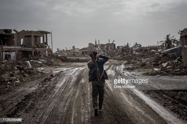 An SDF fighter walks down a empty street amid destruction on February 16, 2019 in As Susah, Syria. Civilians have begun returning to some small towns...