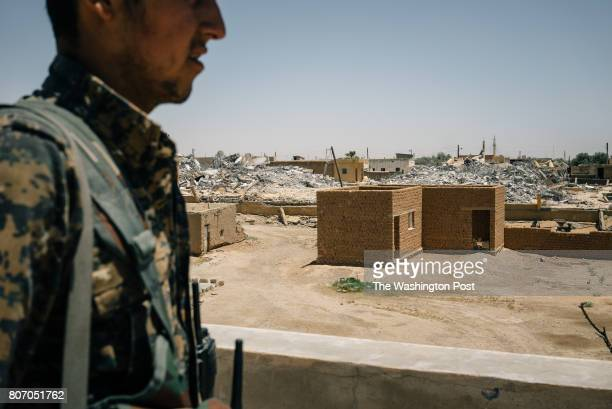 An SDF soldier stands on a rooftop in a position on the western edge of Raqqa city