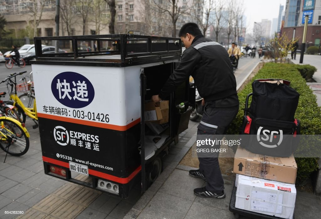 An Sf Express Courier Delivery Rider Sorts Packages In The