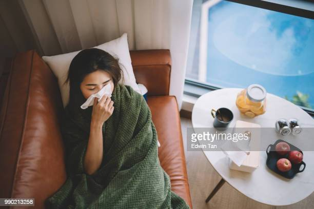 an sick asian chinese female lying on sofa in living room covered with blanket and wiping nose with tissue paper - cold virus stock pictures, royalty-free photos & images