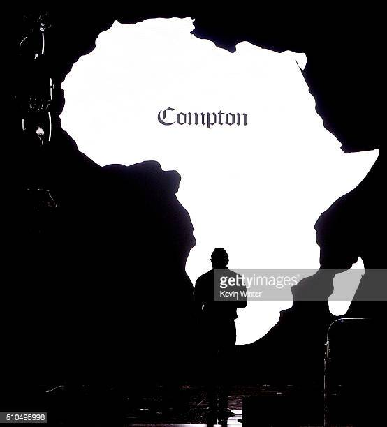 An silhouette of Africa with 'Compton' printed on it is projected onto a video screen as recording artist Kendrick Lamar performs onstage during The...