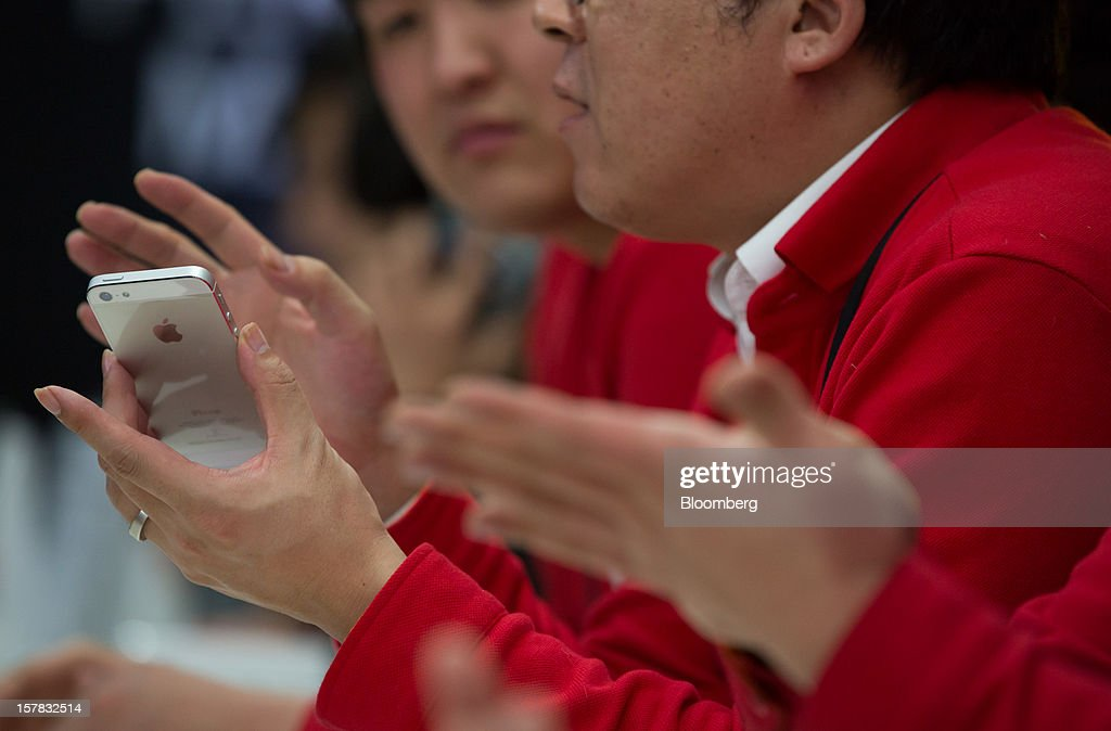 An SK Telecom Co. employee holds an Apple Inc. iPhone 5 during a launch event in Seoul, South Korea, on Friday, Dec. 7, 2012. The iPhone 5 went on sale in South Korea today. Photographer: SeongJoon Cho/Bloomberg via Getty Images