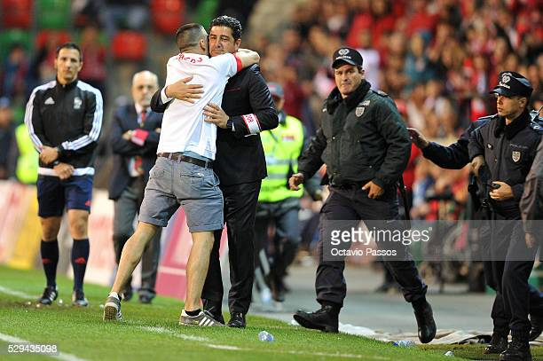 An SL Benfica fan invades the pitch for give an hug to Rui Vitoria SL Benfica coach during the Portuguese Primeira Liga match against CS Maritimo and...
