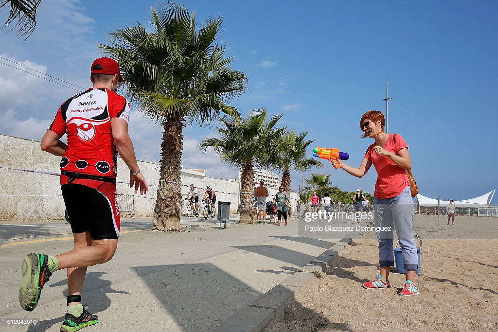 An spectator uses a water gun to throw water at athletes competing during the run leg of Ironman Barcelona on October 2, 2016 near Calella, in Barcelona province, Spain.