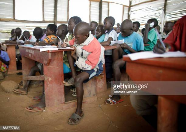 An Students are sitting at school camps in a school at Rhino Refugee Camp Settlement in northern Uganda Here children of local people and refugees...