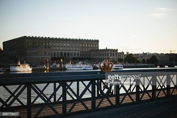 An sunset shot of the a Gilded crown on the Skeppsholmsbron in Stockholm with the Royal Palace in the background.
