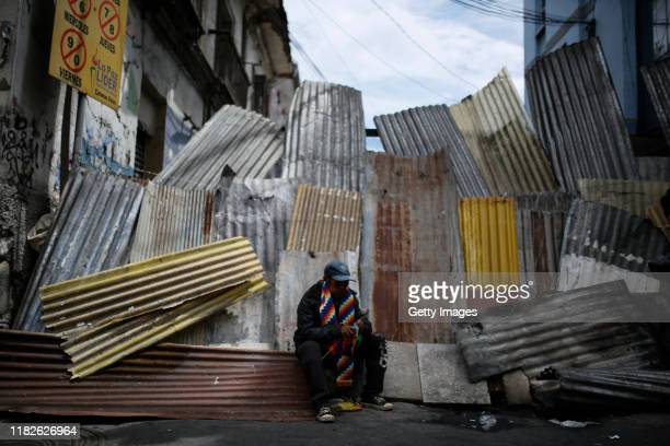 An suporter of Evo Morales wearing a Whipala colors scarf sits on a roadblock during a protest on November 15 2019 in La Paz Bolivia Morales flew to...