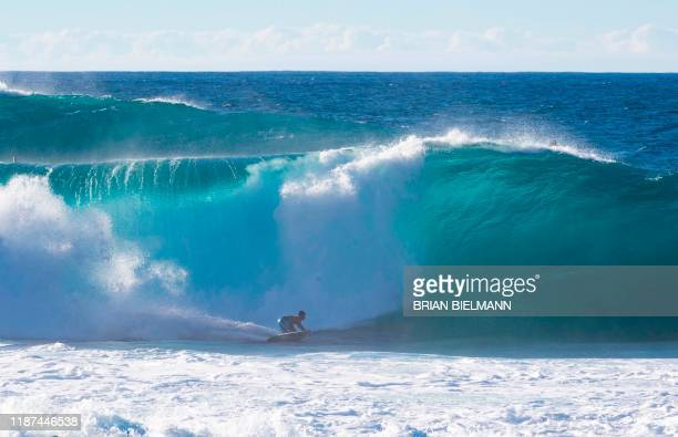TOPSHOT An surfer rides a wave after the Pipe Invitational trials ahead of the Pipeline masters at the north shore of Oahu in Hawaii on December 9...