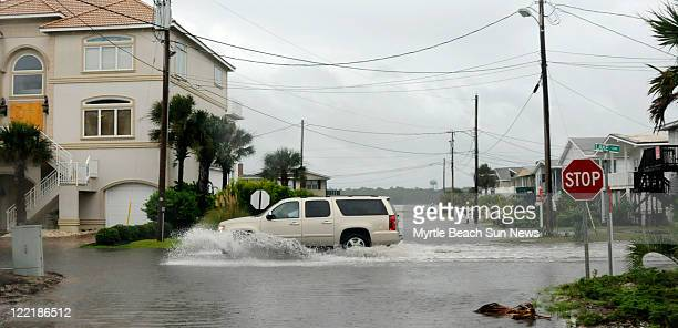 An SUV drives along a flooded portion of Lake Drive in the Cherry Grove section of North Myrtle Beach South Carolina as winds from Hurricane Irene...