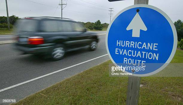 An SUV rides past an evacuation route sign September 17 2003 in Nags Head North Carolina Residents in the Outer Banks are preparing for Hurricane...