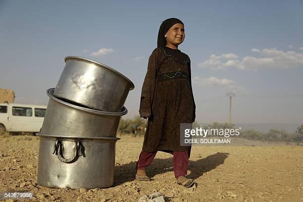 TOPSHOT An Syrian girl stands next to cooking pots as USbacked Kurdish and Arab fighters advance into the Islamic State jihadist's group bastion of...