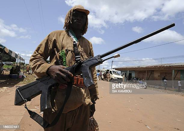 An traditional Ivorian Dozo hunter carrying a rifle poses on September 27 2013 in Kani in the Seguela department 592km from Abidjan after a meeting...