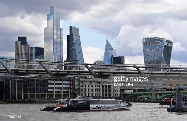 An Uber boat operated in partnership with Thames Clippers, travels along the River Thames as it passes under the Millennium Bridge, backdropped by...