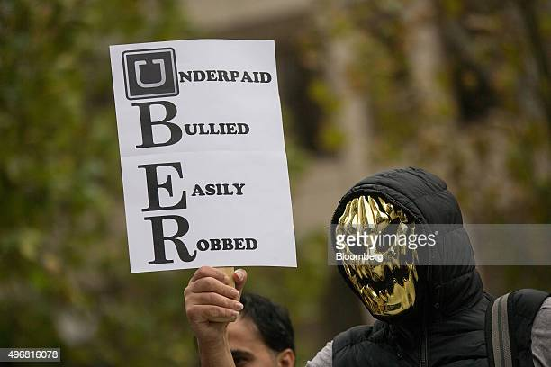 An Uber driver wearing a mask holds up a sign during a protest against a rise in the commission taken by Uber Technologies Inc outside their offices...