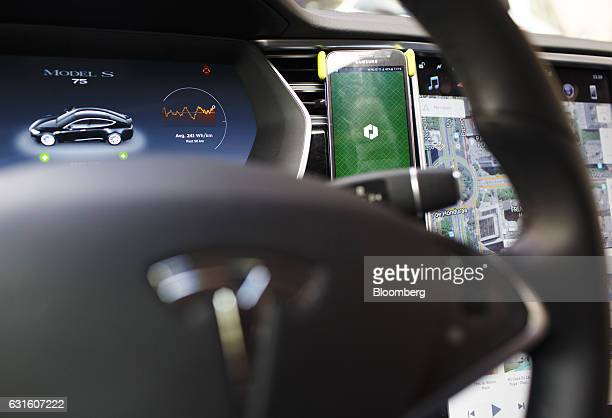 An Uber Technologies Inc app sits on a smartphone inside a Tesla Motors Inc Model S electric automobile in Madrid Spain on Friday Jan 13 2017...