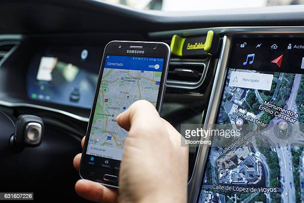 An Uber Technologies Inc driver uses the company's smartphone app in a Tesla Motors Inc Model S electric automobile in Madrid Spain on Friday Jan 13...