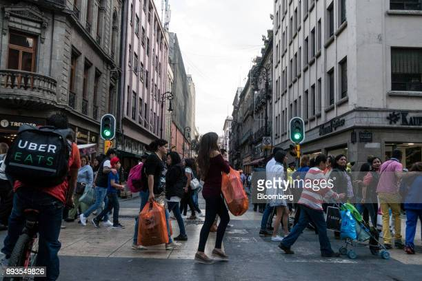 An Uber Technologies Inc Eats bike messenger left passes shoppers and pedestrians near the main square in Mexico City Mexico on Monday Nov 20 2017...