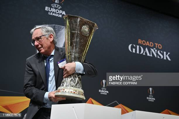 An UEFA official removes the UEFA Europa League football cup trophy after the cup's round of 32 draw ceremony on December 16, 2019 in Nyon.
