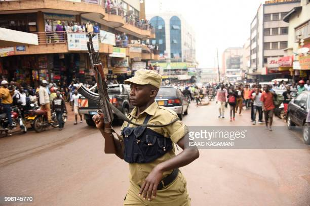 An Ugandan police officer lifts his AK47 riffle aloft opposite protesters during a demonstration on July 11 2018 in Kampala to protest a...