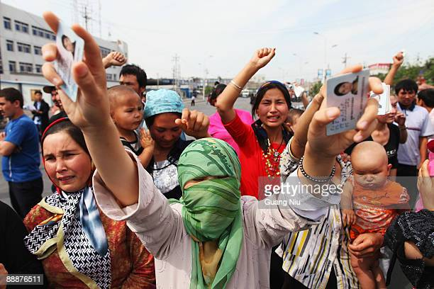 An Uighur woman holds her relatives' ID cards who are are currently detained as she and others protests on a street on July 7 2009 in Urumqi the...