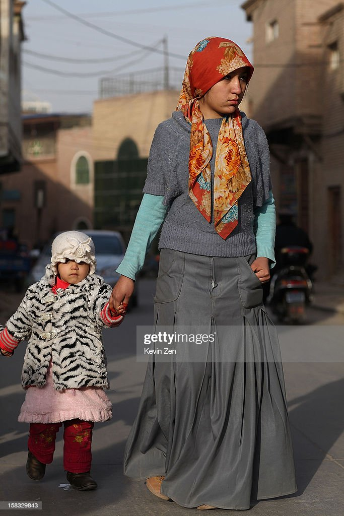 An Uighur woman wears headscarves across the street with a child in Kashgar, on December 10, 2012 in Kashi, China. Kashgar is home to the ethnic Uyghur Muslim community.