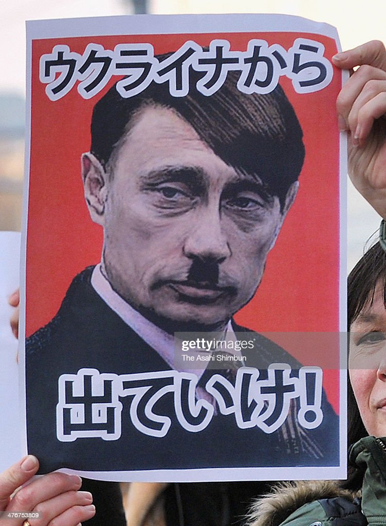 An Ukrainian in Japan holds a photomontage with Putin and Hitler with a message 'Get out from Ukraine' as part of protest demanding the withdrawal of the Russian military from Crimea outside the Russian Embassy on March 4, 2014 in Tokyo, Japan. As the Ukrainian crisis escalates, thousands of Russian Troops have begun to blockade a number of Ukrainian military bases across Crimea.