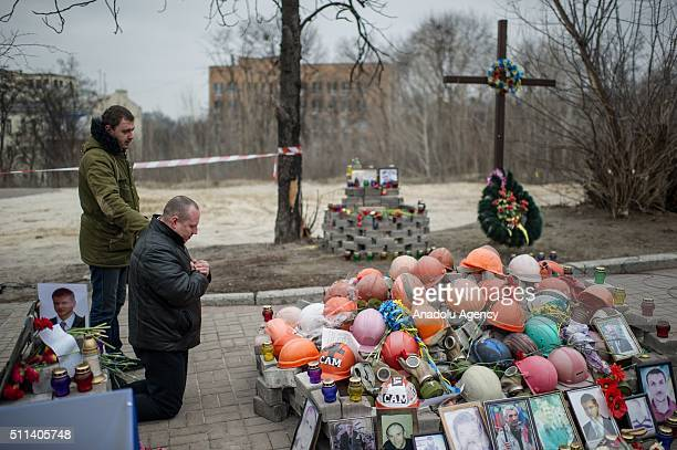 An Ukrainian man kneels next to the portraits and helmets of the Euromaidan protests victims during the second anniversary of the Euromaidan protests...
