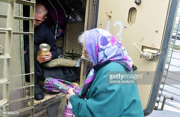 An Ukrainian serviceman gives food to an elderly woman in the eastern Ukrainian city of Kramatorsk on July 7, 2014. Retreating pro-Russian insurgents...