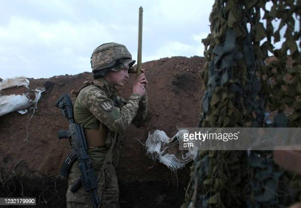 An Ukrainian serviceman uses a periscope in a trench as he stands at his post on the frontline with Russia backed separatists near the town of...