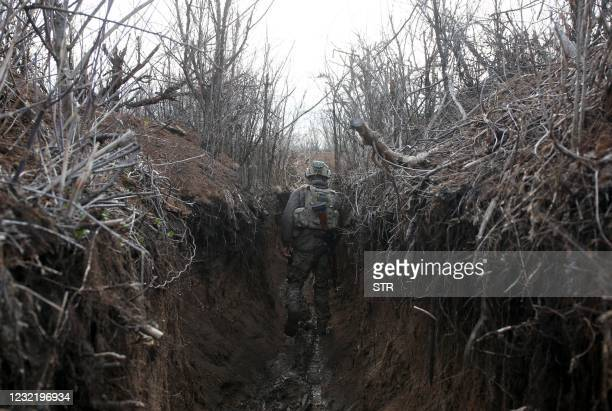 An Ukrainian serviceman walks in a trench as he stands at his post on the frontline with Russia backed separatists near the town of Zolote, in the...
