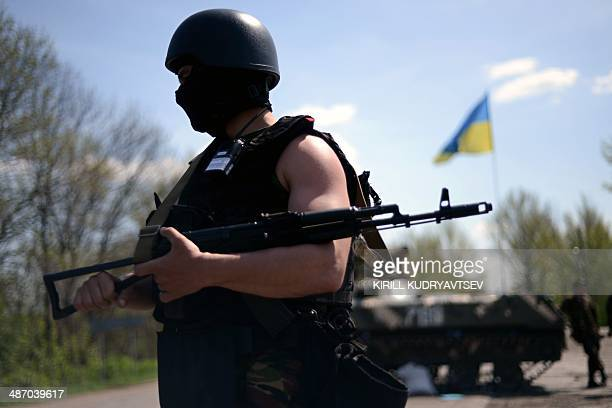 An Ukrainian soldier is pictured in front of an Armoured Personnel Carriers as he guards a checkpoint on the road about 25 km from the eastern...
